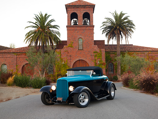AUT 26 RK1207 01 © Kimball Stock 1932 Ford Roadster Hot Rod Black And Turquoise Front 3/4 View On Pavement By Building Palm Trees Sky