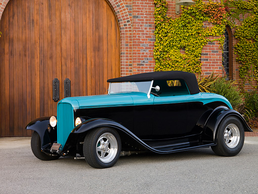 AUT 26 RK1209 01 © Kimball Stock 1932 Ford Roadster Hot Rod Black And Turquoise Front 3/4 View On Pavement By Brick Building Wooden Door