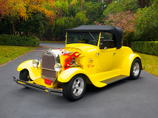 AUT 26 RK1215 01 © Kimball Stock 1929 Ford Hot Rod Yellow Convertible 3/4 Front View On Pavement By Trees