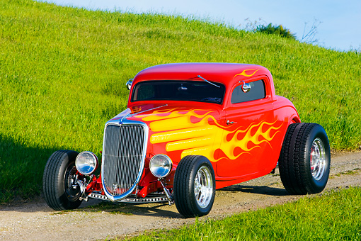 AUT 26 RK1224 01 © Kimball Stock 1934 Ford 3-Window Coupe With Flames 3/4 Front View On Dirt By Grass Hill