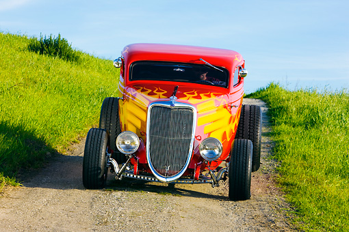 AUT 26 RK1229 01 © Kimball Stock 1934 Ford 3-Window Coupe With Flames Head On View On Dirt By Grass Hill