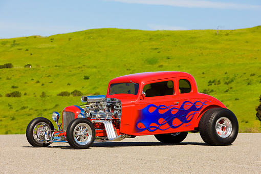 AUT 26 RK1246 01 © Kimball Stock 1934 Chevrolet 5-Window Coupe Hot Rod Red With Blue Flames 3/4 Front View By Grass Hill Blue Sky