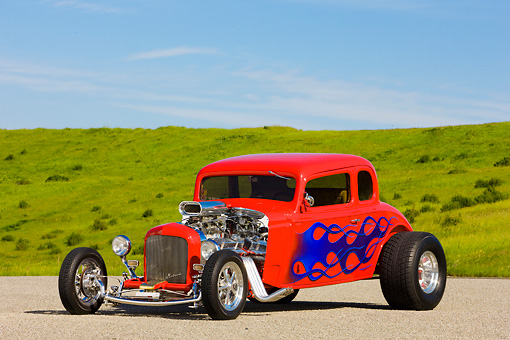 AUT 26 RK1248 01 © Kimball Stock 1934 Chevrolet 5-Window Coupe Hot Rod Red With Blue Flames 3/4 Front View By Grass Hill Blue Sky