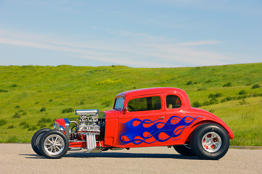 AUT 26 RK1249 01 © Kimball Stock 1934 Chevrolet 5-Window Coupe Hot Rod Red With Blue Flames 3/4 Front View By Grass Hill Blue Sky