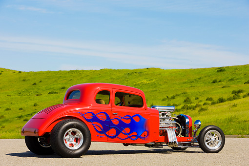 AUT 26 RK1250 01 © Kimball Stock 1934 Chevrolet 5-Window Coupe Hot Rod Red With Blue Flames 3/4 Rear View By Grass Hill Blue Sky