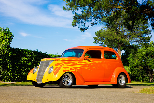 AUT 26 RK1295 01 © Kimball Stock 1937 Ford Sedan Hot Rod Orange 3/4 Front View By Trees Blue Sky