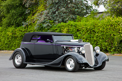 AUT 26 RK1297 01 © Kimball Stock 1934 Chevrolet Phaeton Hot Rod Black 3/4 Front View By Trees Shrubs