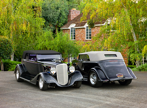 AUT 26 RK1298 01 © Kimball Stock Two 1934 Chevrolet Phaeton Hot Rods Black 3/4 Front & Rear Views By Trees Shrubs