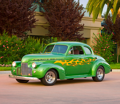 AUT 26 RK2664 01 © Kimball Stock 1940 Chevrolet Coupe Hot Rod Green With Yellow Flames 3/4 Front View On Pavement By Shrubs And Trees