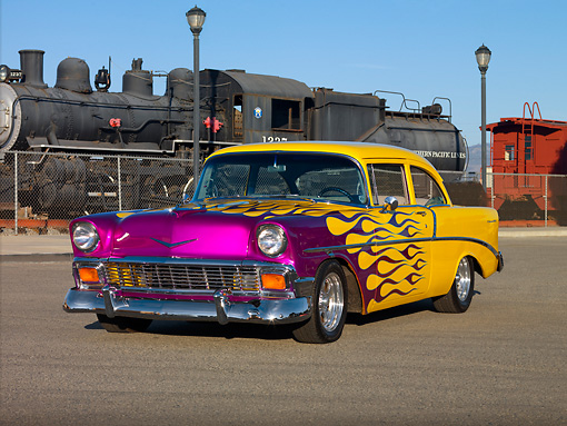 AUT 26 RK2682 01 © Kimball Stock 1956 Chevrolet 210 Post Hot Rod Yellow Purple Flames 3/4 Front View On Pavement By Train