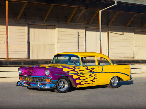 AUT 26 RK2684 01 © Kimball Stock 1956 Chevrolet 210 Post Hot Rod Yellow Purple Flames 3/4 Front View On Pavement By Building