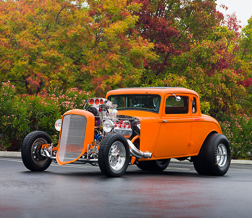 AUT 26 RK2685 01 © Kimball Stock 1934 Plymouth 5-Window Coupe Hot Rod Orange 3/4 Front View On Pavement By Trees