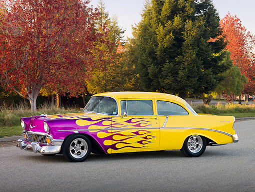 AUT 26 RK2692 01 © Kimball Stock 1956 Chevrolet 210 Post Hot Rod Yellow Purple Flames 3/4 Front View On Pavement By Autumn Trees