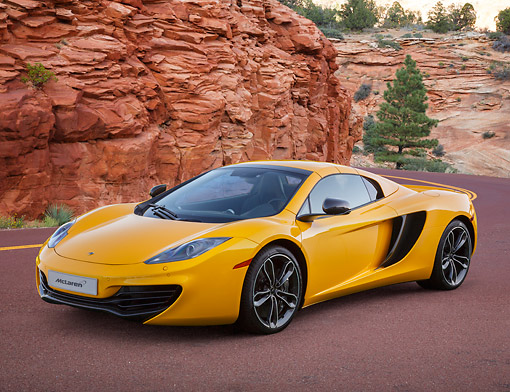 AUT 28 BK0002 01 © Kimball Stock 2013 McLaren 12C Spider Yellow 3/4 Front View On Road By Red Rock And Trees