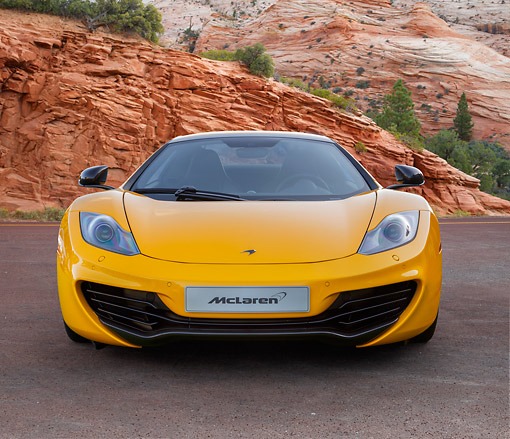 AUT 28 BK0003 01 © Kimball Stock 2013 McLaren 12C Spider Yellow Front View On Road By Red Rock And Trees