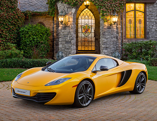 AUT 28 BK0004 01 © Kimball Stock 2013 McLaren 12C Spider Yellow 3/4 Front View On Brick By House