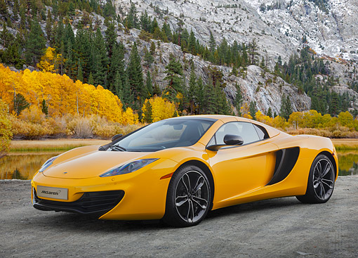 AUT 28 BK0006 01 © Kimball Stock 2013 McLaren 12C Spider Yellow 3/4 Front View On Pavement By Water And Mountains