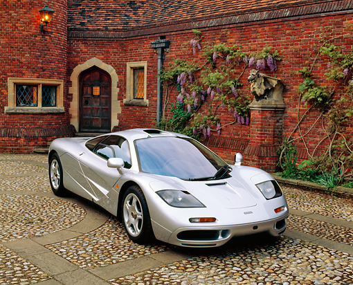 AUT 28 RK0029 01 © Kimball Stock McLaren F-1 Silver 3/4 Front View On Stone Pavement By Brick House