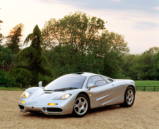AUT 28 RK0041 01 © Kimball Stock McLaren F-1 Silver 3/4 Front View On Gravel With Lights On By Trees At Dusk