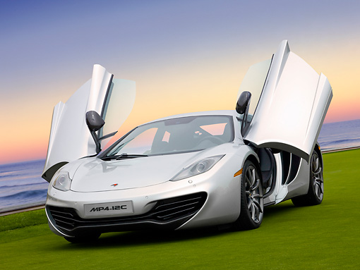 AUT 28 RK0138 01 © Kimball Stock 2012 McLaren MP4-12C Prototype Silver 3/4 Front View On Grass By Building
