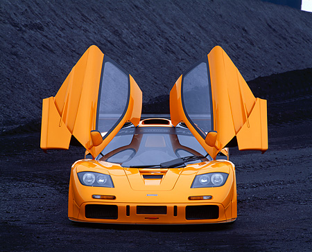 AUT 28 RK0004 07 © Kimball Stock 1996 McLaren F1 LM Orange Head On View With Doors Open On Coal Field