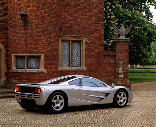 AUT 28 RK0019 03 © Kimball Stock McLaren F1 Silver 3/4 Rear View Stone Pavement And Brick House