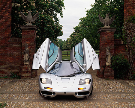 AUT 28 RK0024 06 © Kimball Stock McLaren F1 Silver Head On View With Doors Open In Front Of Gate On Stone Pavement