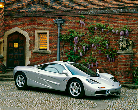 AUT 28 RK0029 02 © Kimball Stock McLaren F-1 Silver 3/4 Front View On Stone Pavement By Brick House