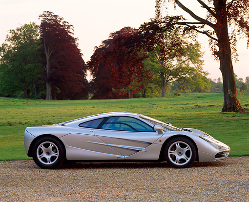 AUT 28 RK0039 01 © Kimball Stock McLaren F-1 Silver Profile On Gravel By Grass And Trees