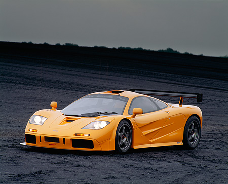 AUT 28 RK0045 04 © Kimball Stock 1996 McLaren F1 LM Orange Front 3/4 View On Black Coal Field Headlights On