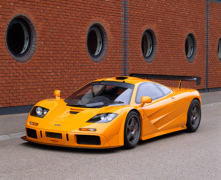 AUT 28 RK0056 07 © Kimball Stock 1996 McLaren F1 LM Orange Front 3/4 View On Pavement By Brick Wall