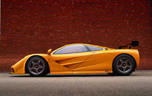 AUT 28 RK0057 07 © Kimball Stock 1996 McLaren F1 LM Orange Profile On Pavement By Brick Wall