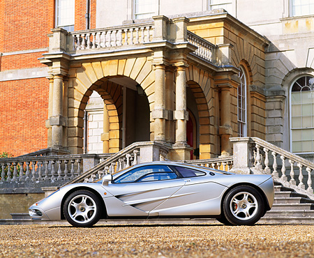 AUT 28 RK0067 05 © Kimball Stock McLaren F1 Silver 3/4 Front View On Gravel By Building And Steps