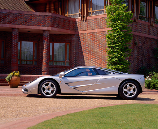 AUT 28 RK0074 02 © Kimball Stock McLaren F1 Silver Profile On Driveway By Grass And Brick Building