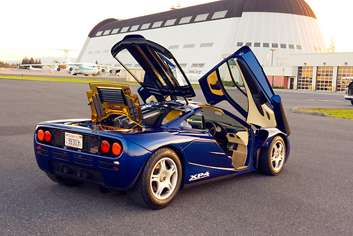 AUT 28 RK0120 01 © Kimball Stock 1993 Mclaren F1 XP4 Blue 3/4 Rear View Doors Open On Pavement By Hangar