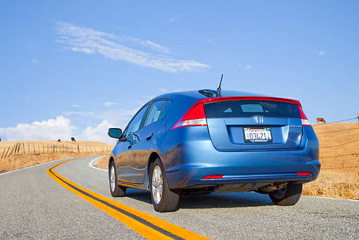 AUT 29 BK0005 01 © Kimball Stock 2010 Honda Insight Blue 3/4 Rear View Driving On Road