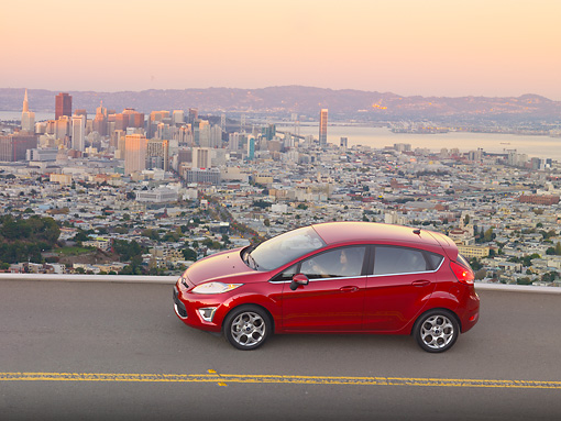 AUT 29 BK0031 01 © Kimball Stock 2011 Ford Fiesta Red Profile View On Road By San Francisco Skyline