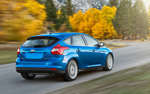 AUT 29 BK0040 01 © Kimball Stock 2014 Ford Focus Titanium Blue 3/4 Rear View On Pavement In Motion By Autumn Trees