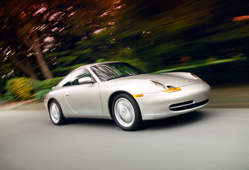 AUT 29 RK0138 10 © Kimball Stock 1999 Porsche 911 Carrera Coupe Silver in motion, 3/4 front on road with trees in background, lights on
