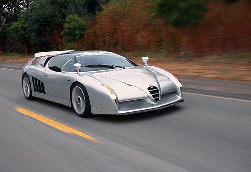 AUT 29 RK0141 06 © Kimball Stock Alfa Romeo Scighera Concept Car Siver 3/4 Front View On Road In Motion By Trees