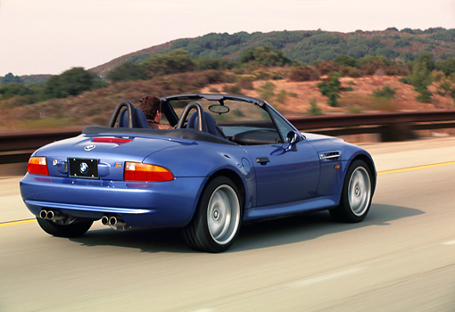 AUT 29 RK0161 04 © Kimball Stock 1999 BMW M Roadster Z3 Convertible Blue 3/4 Rear View On Road In Motion