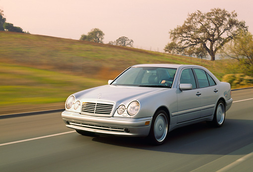 AUT 29 RK0198 50 © Kimball Stock 1999 Mercedes-Benz E55 AMG Silver 3/4 Front View On Road In Motion