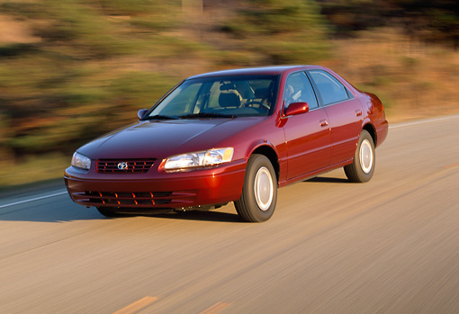 AUT 29 RK0223 08 © Kimball Stock 1999 Toyota Camry CE Pearl Red 3/4 Front View On Road In Motion