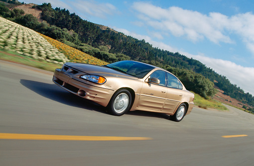 AUT 29 RK0440 01 © Kimball Stock 1999 Pontiac Grand Am Gold Side 3/4 View On Road In Motion