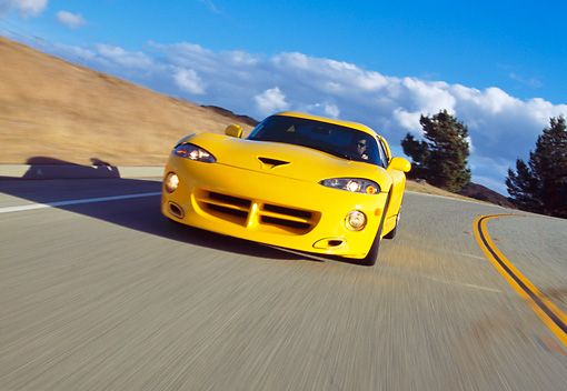 AUT 29 RK0479 04 © Kimball Stock 1996 Hennessey Viper Venom 650R Yellow In Motion On Road Slanted 3/4 Front View Dry Grass Hill Blue Sky