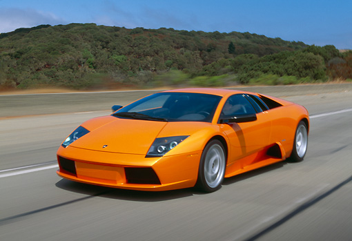 AUT 29 RK0611 17 © Kimball Stock 2002 Lamborghini Murcielago Orange 3/4 Side View On Road In Motion By Trees And Hills