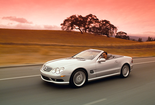 AUT 29 RK0630 04 © Kimball Stock 2003 Mercedes-Benz SL55 AMG Roadster Silver 3/4 Front View On Road In Motion Filtered