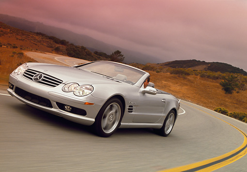 AUT 29 RK0630 20 © Kimball Stock 2003 Mercedes-Benz SL55 AMG Roadster Silver 3/4 Front View On Road In Motion Filtered