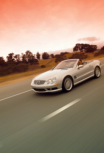 AUT 29 RK0630 28 © Kimball Stock 2003 Mercedes-Benz SL55 AMG Roadster Silver 3/4 Front View On Road In Motion Filtered
