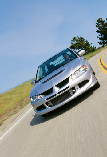 AUT 29 RK0638 24 © Kimball Stock 2003 Mitsubishi Lancer Evolution VIII Silver Slanted 3/4 Front View On Road In Motion